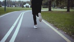 Manspring längs en spolning parkerar vägen tillbaka sikt långsam rörelse Idrottsman i vita gymnastikskor som joggar på en tyst gr arkivfilmer