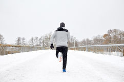 Manspring längs snö täckte vinterbrovägen Royaltyfri Foto