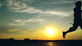 Manspring på gatan i solnedgång stock video
