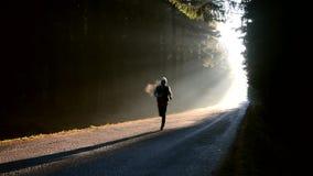 Manspring på soluppgång på den dimmiga skogen stock video