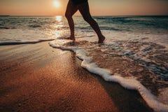 Manspring på stranden på soluppgång royaltyfria bilder