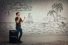 Manställningar bak bagage firar början av ferie som föreställer honom på en exotisk ö arkivbild