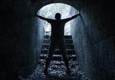 Manställningar i mörk stentunnel med det glödande slutet Royaltyfri Fotografi