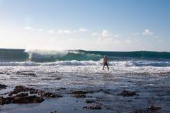 Manstag i vaggastranden och blick på stora vågor solig dag Royaltyfria Foton