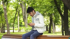 Manstudent med lyssnande musik för smartphone lager videofilmer