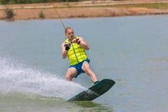 Manstudie som wakeboarding på en blå sjö Arkivbilder
