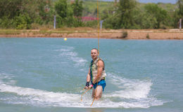 Manstudie som wakeboarding på en blå sjö Fotografering för Bildbyråer