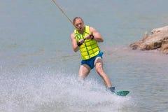 Manstudie som wakeboarding på en blå sjö Arkivbild