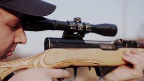 Mansyfte till och med sikten av prickskyttgeväret förberedelse för ett prickskyttskott arkivfilmer