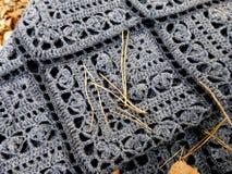 Mantón gris hecho a ganchillo Adornos cuadrados, franja Las hojas de otoño y las agujas del pino cayeron desde arriba imágenes de archivo libres de regalías