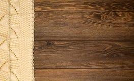 Manta blanca hecha punto en un fondo de madera con el espacio de la copia Fotos de archivo