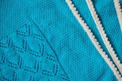 Manta del bebé azul con una frontera blanca, tejida a mano imagenes de archivo