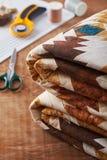 Manta doblada del remiendo en superficie de madera en fondo de costura de los accesorios Fotos de archivo