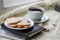 A manta, os diários, as cookies e uma xícara de café encontram-se na janela Imagens de Stock Royalty Free