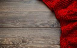 Manta roja hecha punto en un fondo de madera con el espacio de la copia Fotografía de archivo libre de regalías