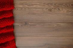 Manta rojiza hecha punto en un fondo de madera con el espacio de la copia Fotografía de archivo libre de regalías