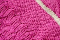 Manta rosada del bebé con una frontera blanca, tejida a mano foto de archivo