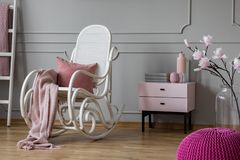 Manta rosada en colores pastel y almohada en la mecedora blanca en sitio sofisticado con el nightstand y las flores en el florero fotografía de archivo