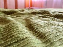 Manta verde en la cama foto de archivo