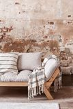 Manta y almohadas modeladas en el sofá gris de madera contra la pared de ladrillo roja en completamente interior imágenes de archivo libres de regalías