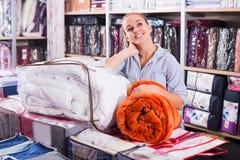 Manta y sobrecama que hacen compras sonrientes del cliente de la muchacha nuevas Imagenes de archivo