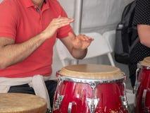 Mantakter på den röda congaen trummar med kala händer med folkmassan arkivfoton
