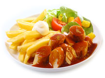 Mantaplatte and gravy or BBQ sauce. Mantaplatte topped with gravy or BBQ sauce served with golden French fries and fresh mixed leafy green salad on white Stock Photo
