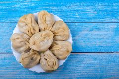Mantas deliciosos em uma placa branca no fundo de madeira azul, culinária asiática, prato nacional tradicional foto de stock