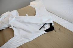 Manteau blanc sur le lit Images stock