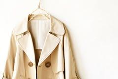 Manteau de fossé élégant beige d'isolement au-dessus du blanc images libres de droits