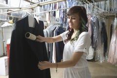 Manteau de nettoyage de propriétaire avec la brosse dans la blanchisserie images libres de droits