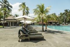 Manteau de paume de plage de Kuta, lieu de villégiature luxueux avec la piscine et lits pliants Bali, Indonésie Photographie stock