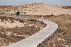 Manteau de pluie rose marchant par des dunes de sable Photographie stock libre de droits