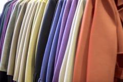 Manteau multicolore sur un cintre dans un magasin d'habillement photos stock