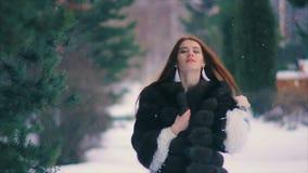 Manteau riche de taille de femme de brune de fourrure brune sur le fond du mouvement lent d'arbre de Noël banque de vidéos
