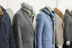 Manteaux de sport de tweed du ` s d'hommes avec des écharpes dans le magasin d'habillement photo libre de droits