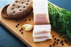 Manteca de cerdo salada con pimienta negra, ajo y eneldo en un fondo de madera Fotos de archivo libres de regalías