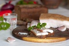 Manteca de cerdo salada del cerdo (salo) en el pan de centeno y la vodka Imagenes de archivo