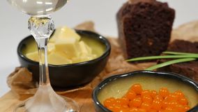Manteiga cortada, caviar, pão preto A bacia de caviar vermelho com colher serviu com pão, manteiga e as ervas cortados no branco filme