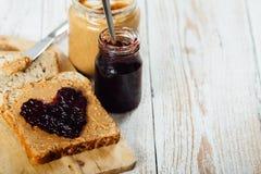 Manteiga de amendoim caseiro e sanduíche da geleia no fundo de madeira fotos de stock royalty free