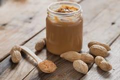 Manteiga de amendoim cremosa na tabela de madeira Foco seletivo Imagens de Stock