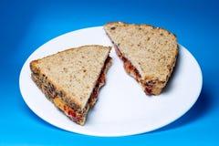 Manteiga de amendoim e sanduíche da geleia na placa de vidro branca imagens de stock