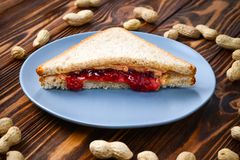 Manteiga de amendoim e sanduíche da geleia no fundo de madeira fotos de stock royalty free