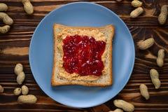 Manteiga de amendoim e sanduíche da geleia no fundo de madeira foto de stock royalty free