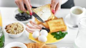 Manteiga de espalhamento da mão fêmea do close-up no brinde do pão fritado usando a faca que aprecia o alimento de café da manhã vídeos de arquivo