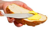 Manteiga de espalhamento da mulher no pão isolado Imagens de Stock Royalty Free