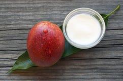 Manteiga do corpo da manga em uma bacia de vidro e um fruto e uma folha orgânicos maduros frescos da manga no fundo de madeira ve Fotografia de Stock