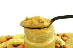 Manteiga e amendoins de amendoim inteiros e descascados no fundo branco Foto de Stock
