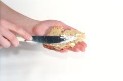 Manteiga e pão nas mãos Fotos de Stock Royalty Free