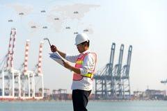 Manteknikern som arbetar med behållarelastfrakter, sänder i skeppsvarv på skymning för logistisk import royaltyfri foto